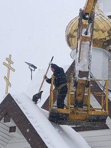 Помощь в уборке снега с крыши храма